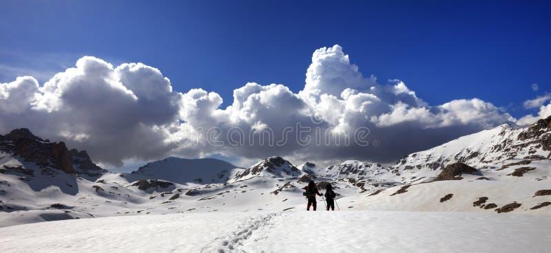 Vue panoramique sur le plateau neigeux avec deux randonneurs et ciel bleu image stock