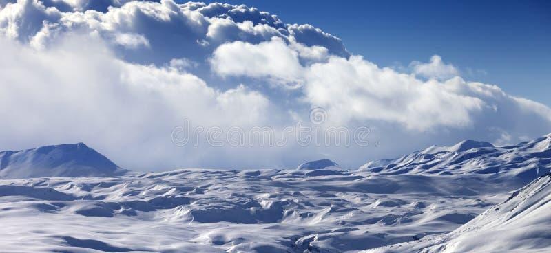 Vue panoramique sur le plateau neigeux de lumière du soleil et le ciel bleu avec des nuages photo libre de droits