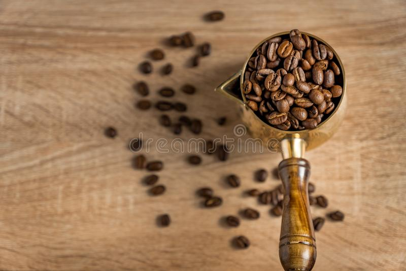 Vue panoramique sur les fèves de café fraîchement rôties dans une tasse de café turquoise traditionnelle sur une table en bois Fo photographie stock