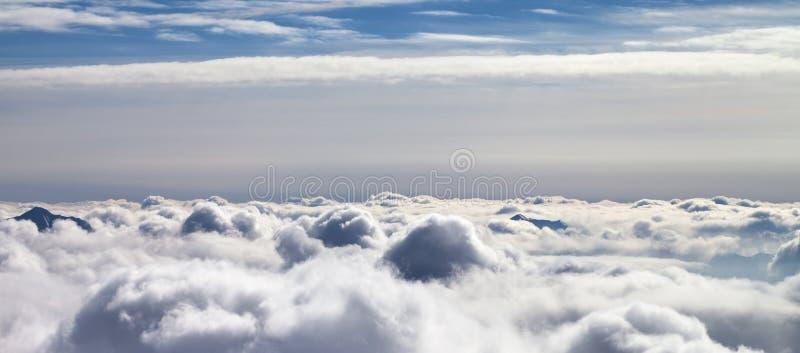 Vue panoramique sur les montagnes neigeuses couvertes de beaux nuages de lumière du soleil images stock