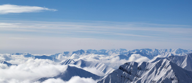 Vue panoramique sur les montagnes neigeuses en nuages image stock