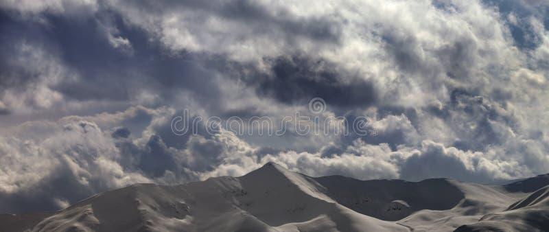 Vue panoramique sur les montagnes neigeuses et le ciel ensoleillé nuageux photos stock