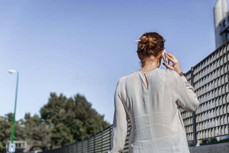 Vue par derrière d'une femme mince parlant à son téléphone portable photo stock