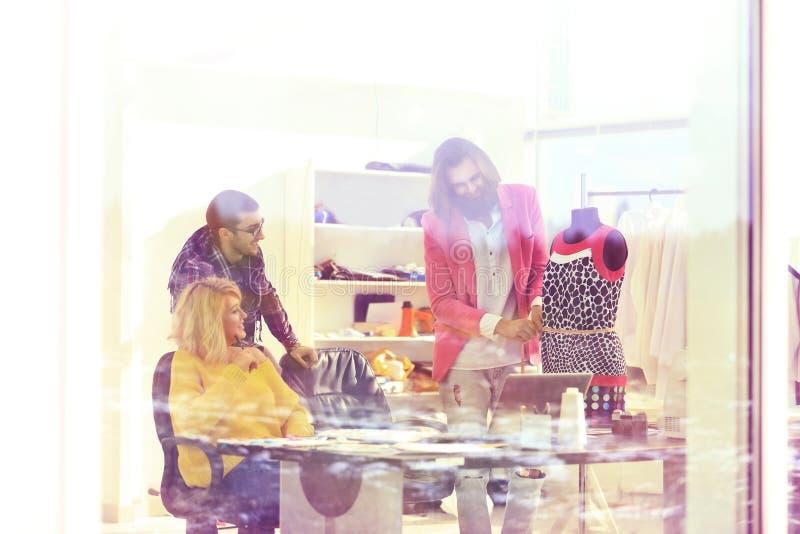 Vue par derrière le verre couturiers discutant de nouvelles conceptions des vêtements photos libres de droits