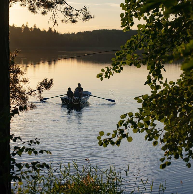 Vue par des arbres sur le lac avec un bateau et un ciel de coucher du soleil photos libres de droits