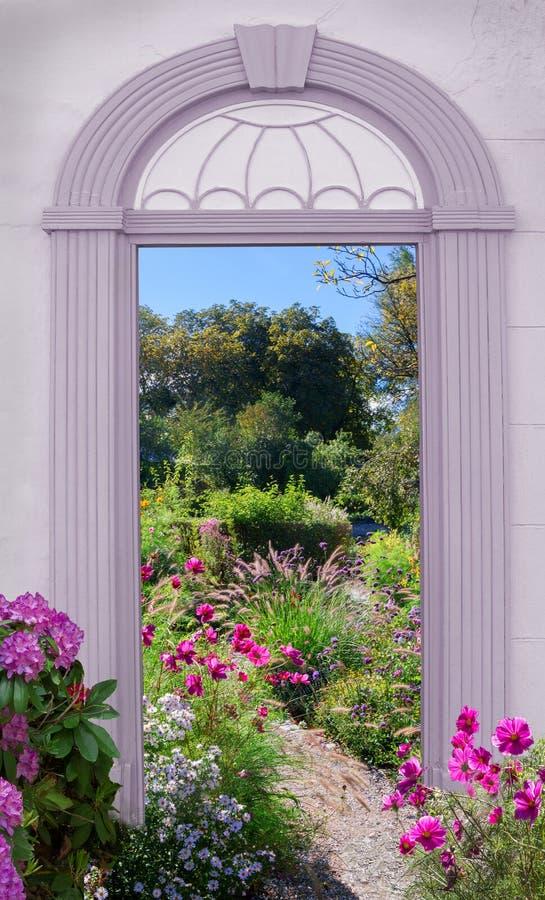 Vue par la porte arquée, parc avec des fleurs d'été photo stock