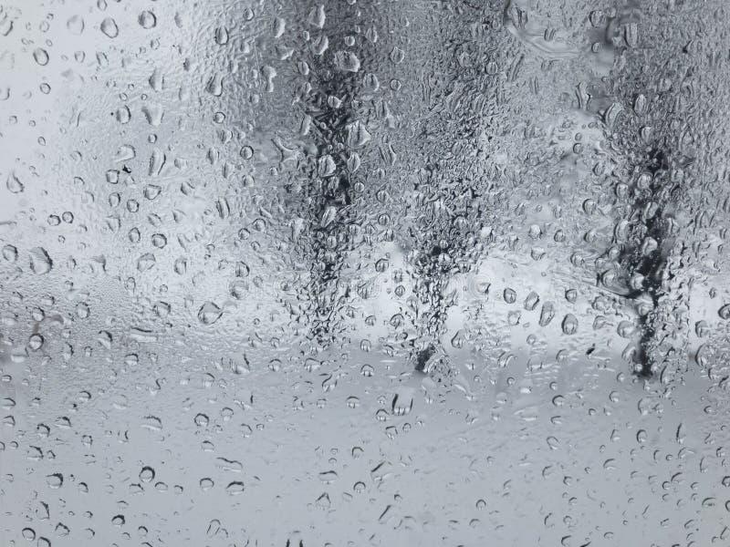 Vue par le dropson de l'eau une fenêtre de voiture pleurante sur des threes photos stock