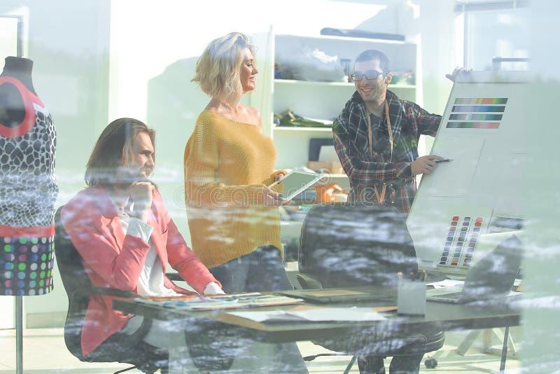 Vue par le mur de verre un groupe de couturiers discutant de nouvelles idées photos libres de droits
