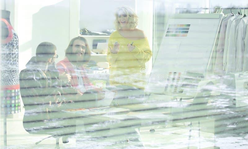 Vue par les abat-jour un groupe de couturiers dans un studio moderne photo stock