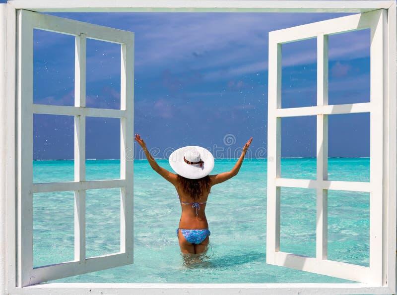 Vue par une fenêtre à une femme attirante dans le bikini photographie stock libre de droits