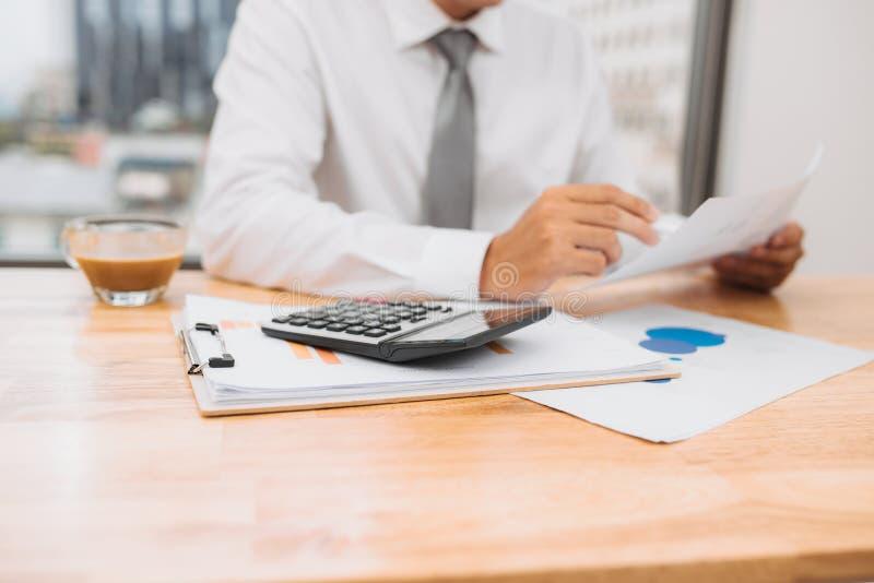 Vue partielle d'homme d'affaires avec le fonctionnement de calculatrice sur le lieu de travail avec les documents et l'ordinateur image stock