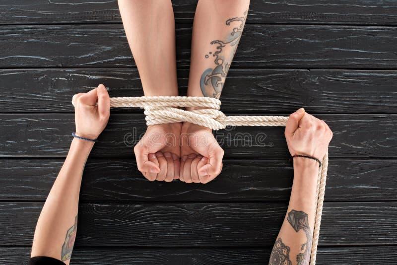 vue partielle de femme attachant la corde autour des mains de mâles sur la surface en bois foncée photo libre de droits