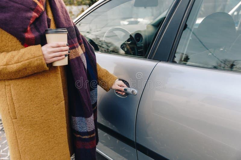 vue partielle de femme avec du café à aller disponible tenant la voiture photos stock