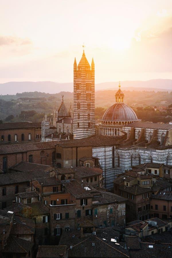 Vue rétro-éclairée pittoresque de Siena Cathedral Santa Maria Assunta (Duomo) de tour de Torre del Mangia à l'heure d'or de couch images libres de droits