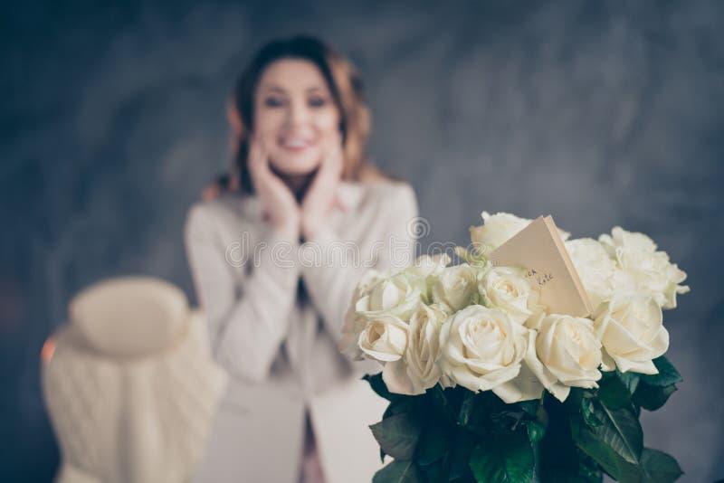 Vue rapprochée portrait de jolies roses blanches fraîches pour une joyeuse et joyeuse femme-directrice mûre floue vacances profes image libre de droits