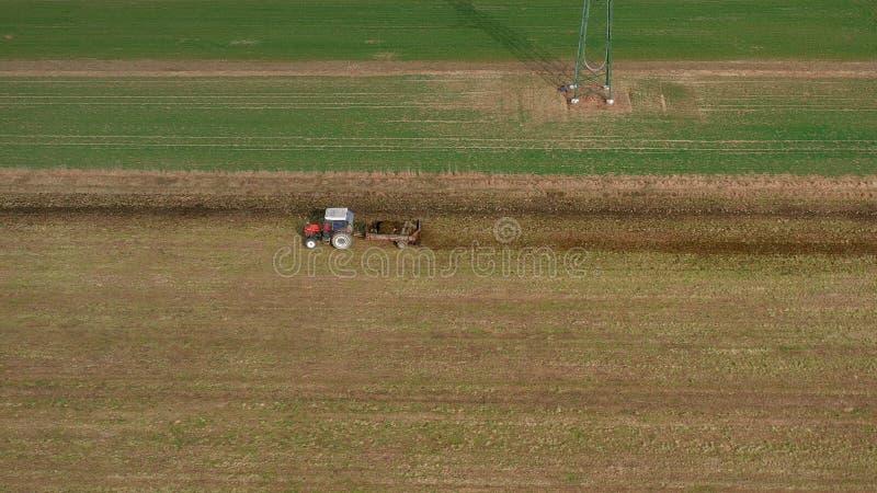 Vue a?rienne d'un tracteur et d'une remorque rouges supportant une charge d'engrais sur la route photos stock