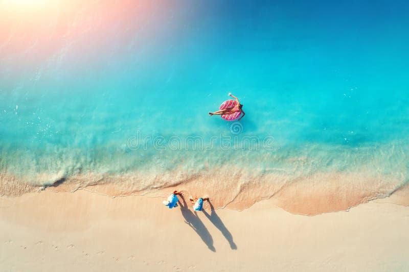 Vue a?rienne d'une femme de natation en mer au coucher du soleil photos stock