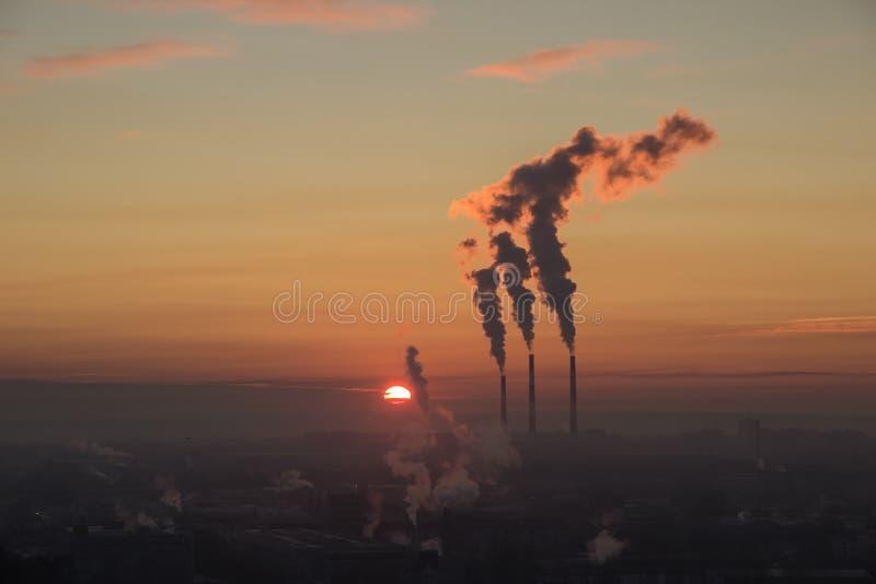 Vue a?rienne de lever de soleil au-dessus de zone industrielle dans la ville Comies rouges du soleil  fum?e venant du tuyau de ce photo libre de droits