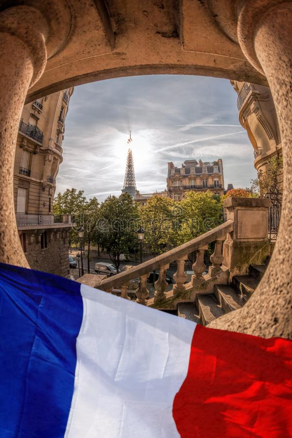 Vue romantique de rue avec Tour Eiffel contre le drapeau français à Paris, France photographie stock libre de droits