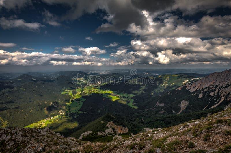 Vue scénique avec foncé, bleu, nuageux, ciel de plateau de Rax, gisements de blocaille et forêt verte photos libres de droits