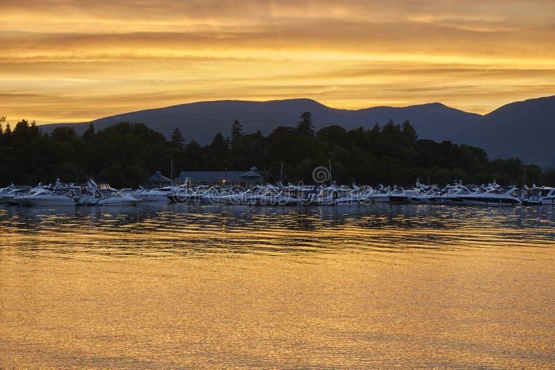 Vue scénique colorée de coucher du soleil des bateaux flottant sur le lac loch lomond en Ecosse, Royaume-Uni image libre de droits