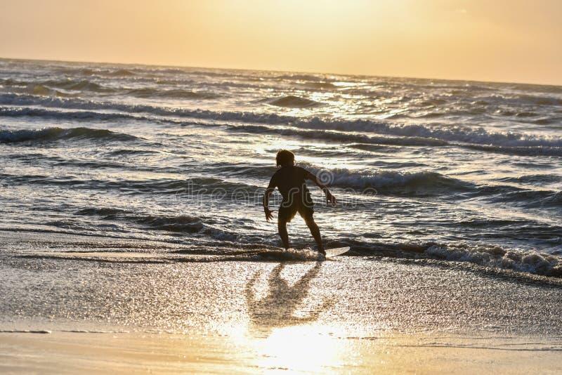 Vue scénique de coucher du soleil de plage tropicale avec un garçon ayant l'amusement avec des vagues d'eau photographie stock libre de droits