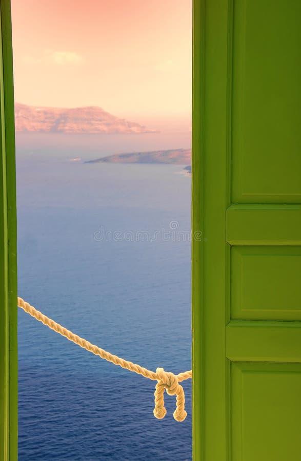 Vue scénique de mer Égée au coucher du soleil par la porte verte ouverte Oia, île de Santorini, Grèce photographie stock libre de droits