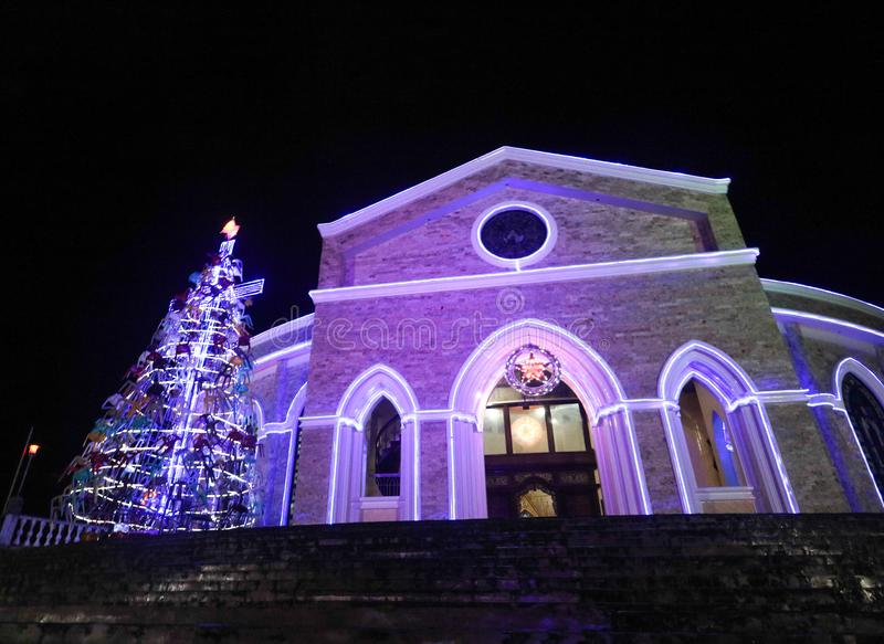 Vue scénique de nuit d'une église lumineuse avec un arbre de Noël énorme photographie stock
