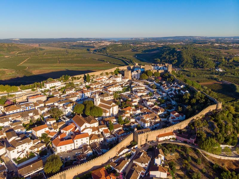 Vue scénique des toits carrelés rouges de maisons blanches, et château de mur de forteresse Village d'Obidos photos libres de droits