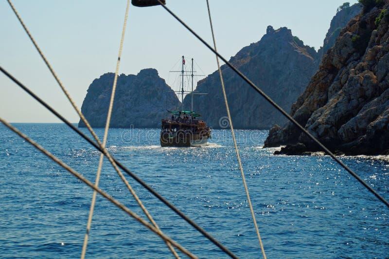 Vue scénique par le cordage d'un bateau à voile touristique dans les eaux de turquoise de la mer Méditerranée avec un bateau image stock