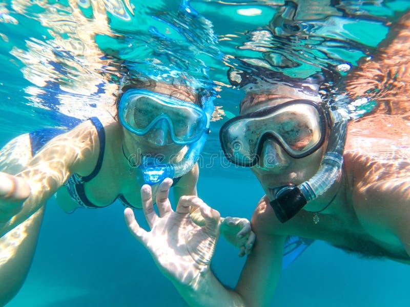 Vue sous-marine des couples naviguants au schnorchel en mer images stock