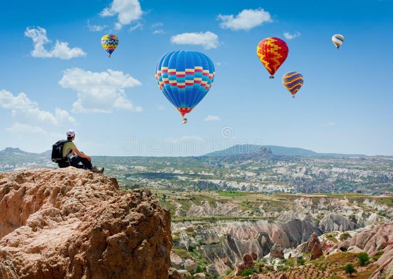 Vue stupéfiante avec la fille s'asseyante de sport et beaucoup de ballons à air chauds Parc national Anatolie, Cappadocia, Turqui photographie stock libre de droits
