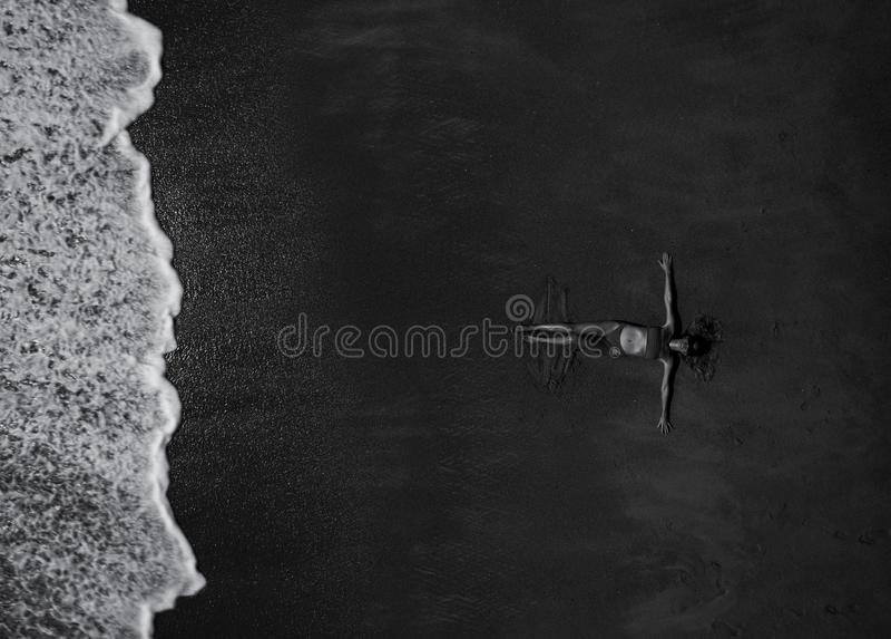 Vue supérieure aérienne de femme avec son pose tendue par mains sur la plage sablonneuse images libres de droits
