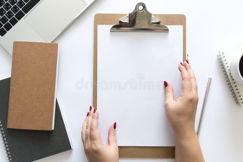 Vue supérieure au-dessus du bureau fonctionnant avec les carnets, le papier chez des mains du ` s de la femme, le stylo, le crayo photos stock