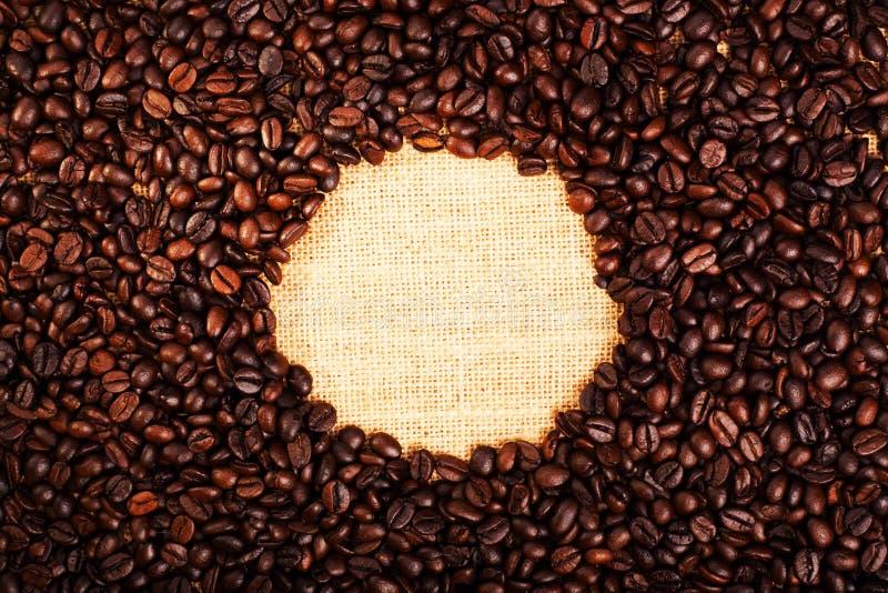Vue supérieure avec l'espace de copie, grains de café rôtis avec le fond de toile de jute photos stock