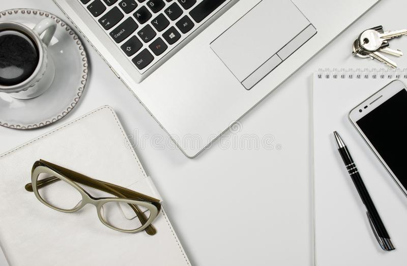 Vue supérieure blanche de table de bureau, ordinateur portable, tasse de café, téléphone portable, verres, bloc-notes de crayon e image stock