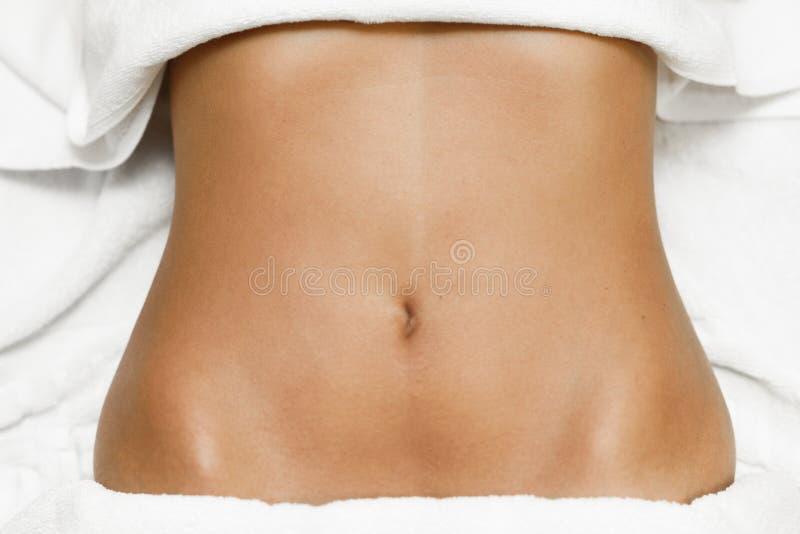 Vue supérieure d'abdomen femelle s'étendant sur le lit de station thermale avec les serviettes blanches photographie stock libre de droits