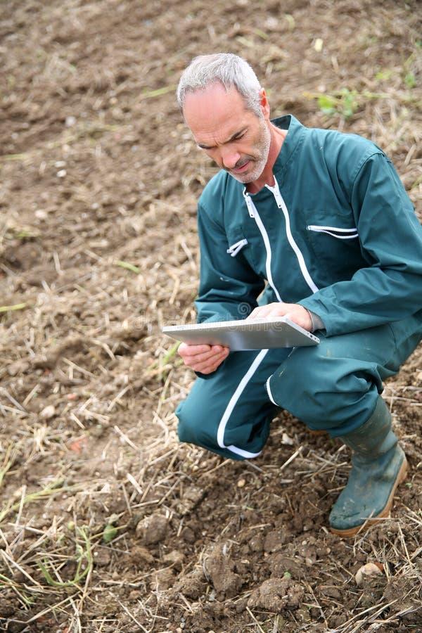 Vue supérieure d'agriculteur se mettant à genoux dans le domaine et à l'aide du comprimé photo stock