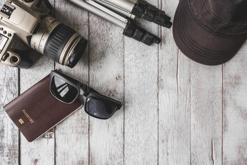 Vue supérieure d'appareil-photo avec le trépied, le chapeau, les lunettes de soleil et le passeport sur la table image stock