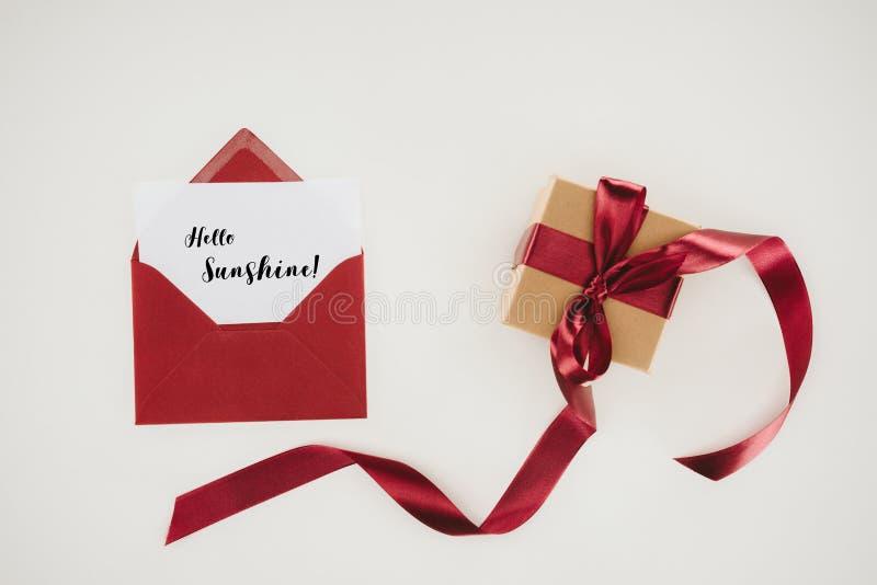 vue supérieure d'enveloppe rouge avec bonjour le lettrage de soleil sur le papier et le boîte-cadeau photographie stock