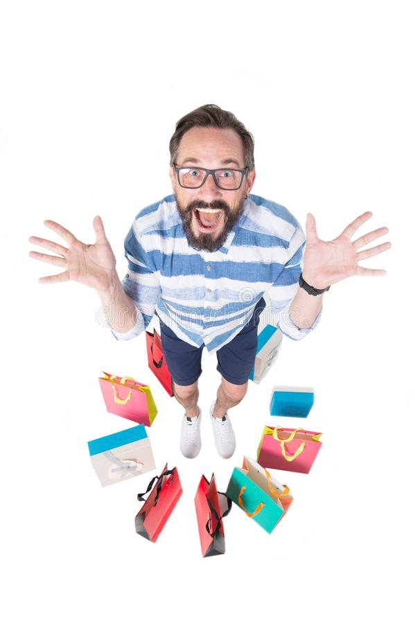 Vue supérieure d'homme enthousiaste souriant tout en ayant des achats près de lui photographie stock