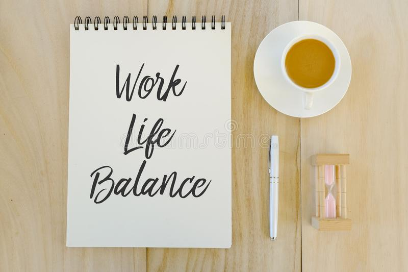 Vue supérieure d'horloge de sable, un chup de café, stylo et carnet écrits avec l'équilibre de la vie de travail sur le fond en b photos stock