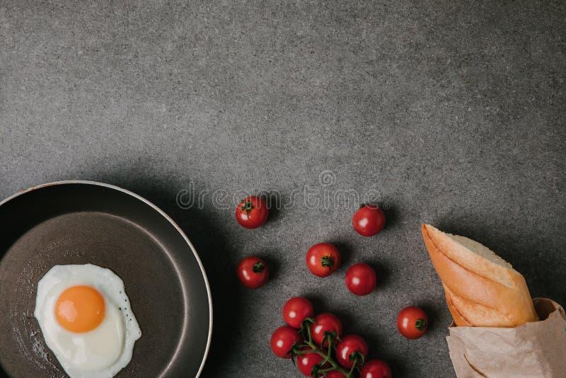 vue supérieure d'oeuf au plat sur la poêle, les tomates fraîches et la baguette dans le sac de papier sur le gris images stock