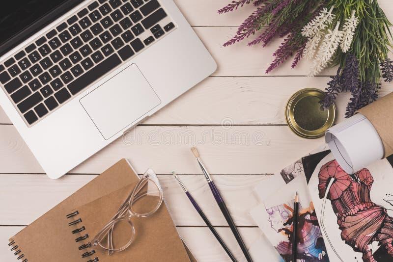 vue supérieure d'ordinateur portable, de fleurs, de modèle, de carnets avec des lunettes et de croquis de mode sur en bois image libre de droits
