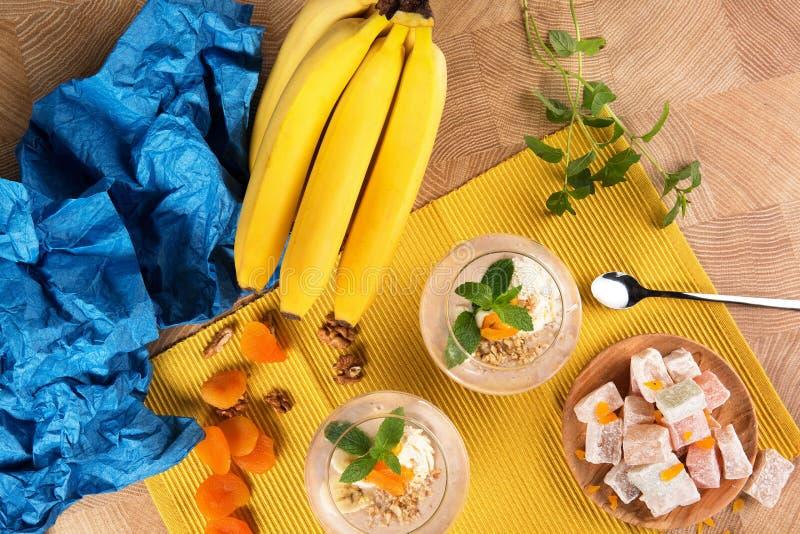 Vue supérieure d'un bel ensemble coloré de bananes, de plaisir turc, et de desserts doux de fruit sur un fond en bois clair photo stock
