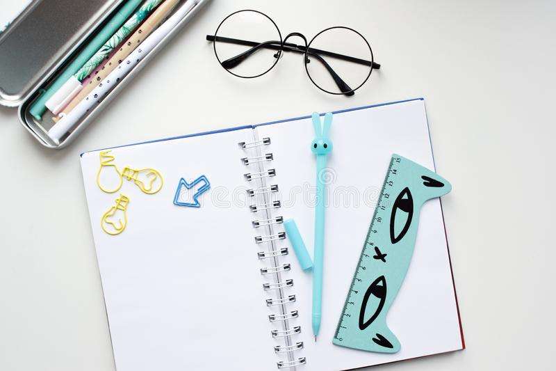 Vue supérieure d'un carnet vide ouvert avec un stylo en forme de lièvres bleu, une règle avec un chat, verres image stock