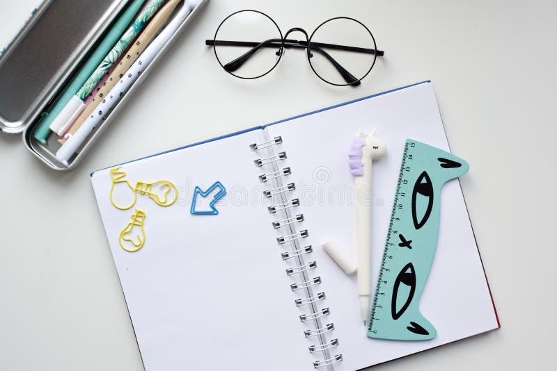 Vue supérieure d'un carnet vide ouvert avec un stylo sous forme de licorne, une trousse d'écolier avec des stylos de kawaii photographie stock