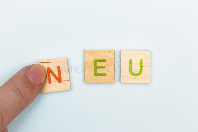 Vue supérieure d'un doigt glissant la lettre N sur l'UE de lettres, moyens de neu dans nouveau allemand photos libres de droits