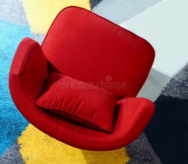 Vue supérieure d'un fauteuil rouge sur un tapis coloré photo stock