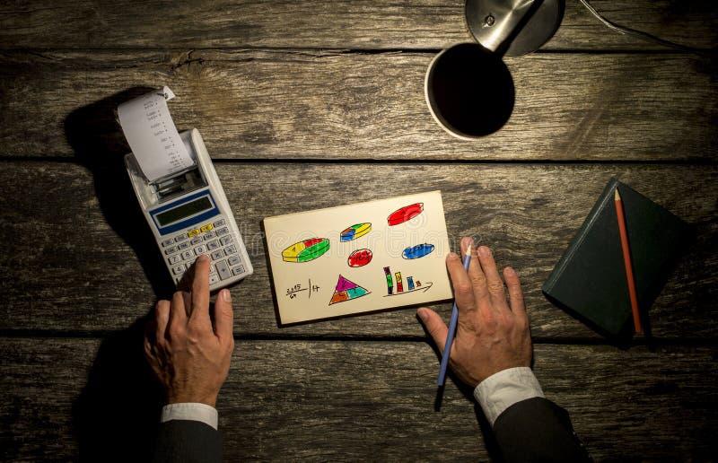 Vue supérieure d'un homme à l'aide de la calculatrice avec le document imprimé sortant photos stock